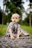 Sad baby girl sitting on the alley of stones