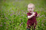 Smiling little baby in a meadow