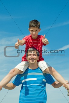 child in a red shirt sitting on his father