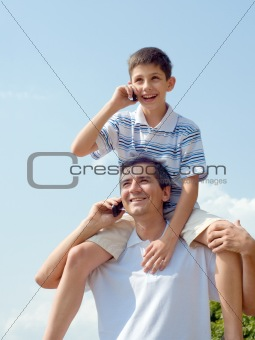 father and his son are speaking over mobiles