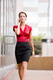 Business woman walking while talking on her phone