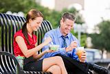Man and Woman Sitting on a Bench and Eating Lunch