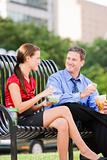 Man and Woman Eating Lunch on Park Bench