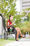 Woman Sitting On a Park Bench Eating Her Lunch