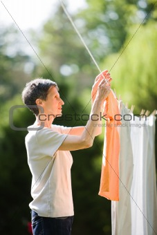 Older Woman Hanging Laundry on Clothesline