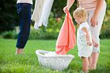 Child Looking at Clothes Basket While Women Hang Laundry to Dry