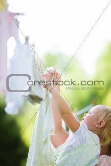 Toddler Helping Mom Hang Laundry on Clothesline
