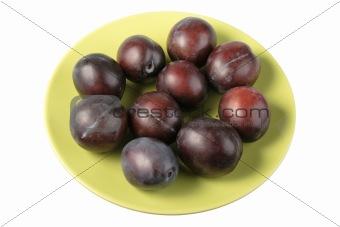 Group of dark-purple plums on plate.