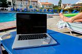 laptop and a mobil phone beside a pool