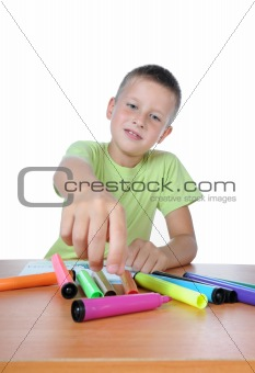 boy drawing on paper with crayons 