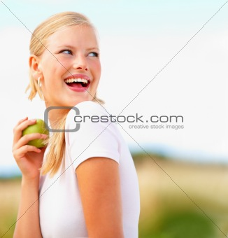 Pretty girl eating a green apple looking away, outdoors