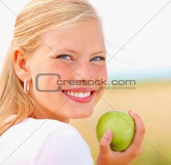 Cute young female holding an apple outdoors