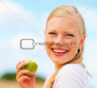Happy young female holding an apple while outside