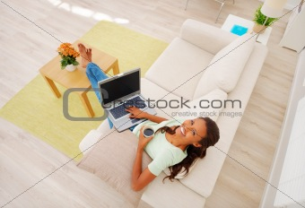 An African American girl using laptop, isolated at home