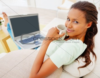 A happy woman using laptop isolated at home