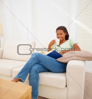 Cute happy female having a beverage while reading