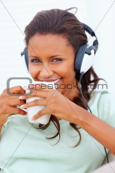 Happy young woman listening to music, drinking a cup tea