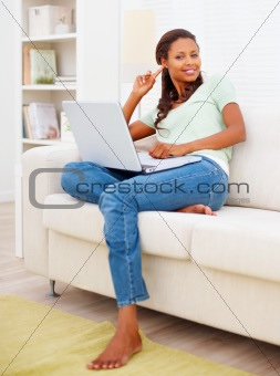 Pretty woman on sofa using a laptop