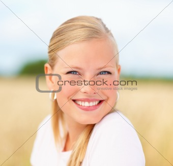 Pretty blond girl smiling at a field