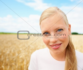 Pretty woman smiling at a field