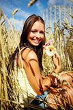 Portrait of a sweet young female with flower at a crop field