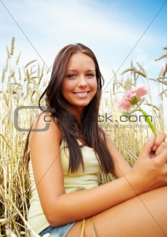 Portrait of a cute young female with flower at a crop field
