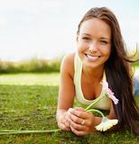 Lovely young female lying on grass field while holding a flower