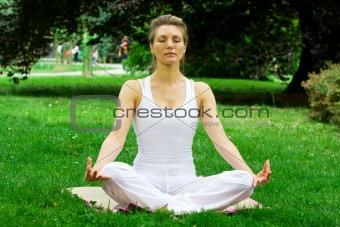 Blonde girl in park doing yoga
