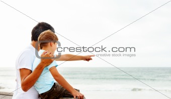 Son pointing towards the sea, showing something to his father
