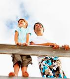 Happy father and son standing on a wooden railing outdoors