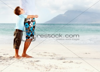Little boy embracing his dad from behind, playing at the sea sho