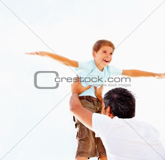 Happy cute boy being lifted up by his father, against the bright