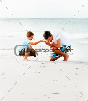 Father and son hearing a shell while at the beach