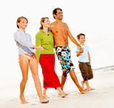 Happy family on a beach vacation, walking on the sea shore