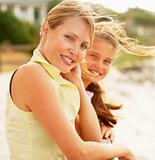 Happy mature female at the beach with her teenage daughter at th