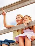 Upward view of a pretty woman sitting with daughter by a wooden