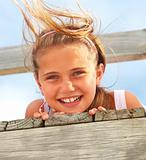Closeup of a sweet teen girl lying on a bridge on a windy day