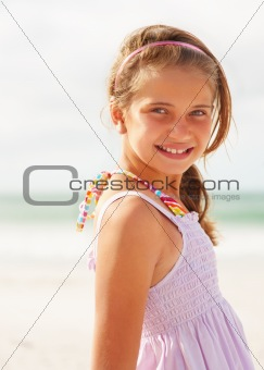 Cute young teenaged girl smiling while at the beach