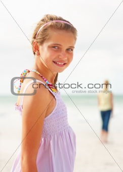 Pretty teenaged girl smiling while at the sea shore