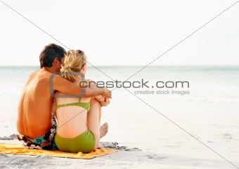 Beach vacation - Rear view of a couple sitting on the sea shore