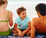 Family relaxing at the beach, focus on small boy