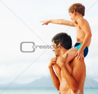 Happy man carrying his son on the shoulders while pointing away