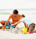 Father helping his son make sand castles at the beach