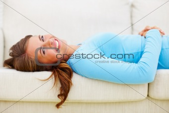 Pretty young female in blue lying on a couch