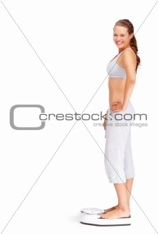 Fit young woman standing on a weighing scale isolated on white