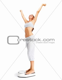 Weight loss - Fit young girl on a weighing scale with hands rais