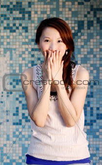 beautiful Asian lady in front of mosaic and laughing