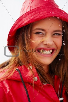 Closeup portrait of a cute young girl in a red raincoat