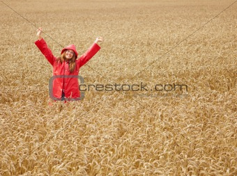 Cute female with her hands raised out in the open farm, wearing