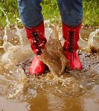 Low section of a female splashing in a muddy puddle